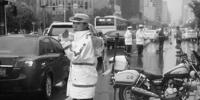 路面突然塌陷女交警站雨中疏导交通 - Syd.Com.Cn